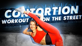 Contortion workout on the street. Flexible ballerina Victoria stretching.