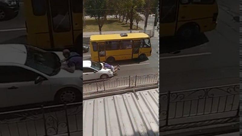 В центре Симферополя водитель пытается сбросить мужика зацепившегося за капот