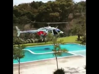 """A helicopter from the """"policia del proteccion civil, jalisco"""", borrows water from a local hotel while fire fighting at """"del bosq"""