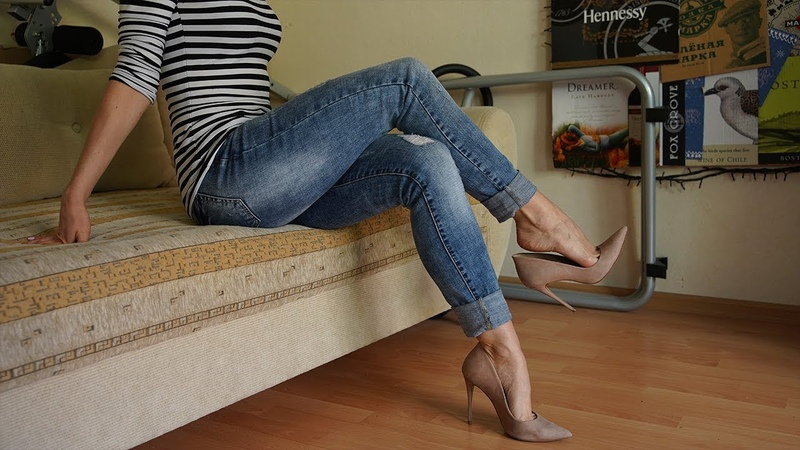 Cute girl in jeans shows her feet, legs and changes the shoes